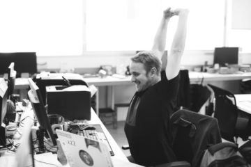 Man stretches his shoulders at the office